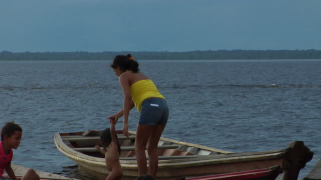 vídeos de stock, filmes e b-roll de slo mo ms pan family with three children hanging over rowboats / tefe, amazonas, brazil - 20 segundos ou mais