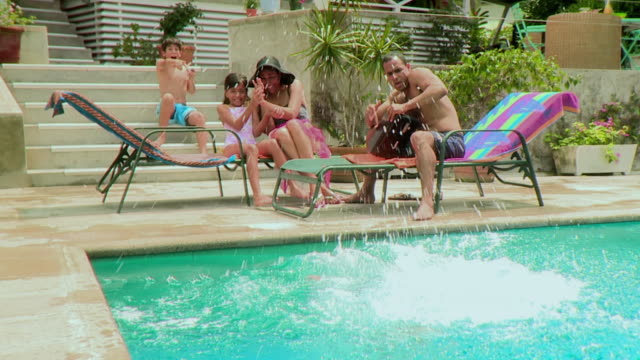 MS Family with three children (7-12) relaxing by pool, boy jumping into water, Panama City, Panama