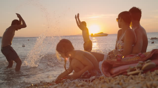 super slo mo family with three children relaxing on the beach at sunset - family with three children stock videos & royalty-free footage