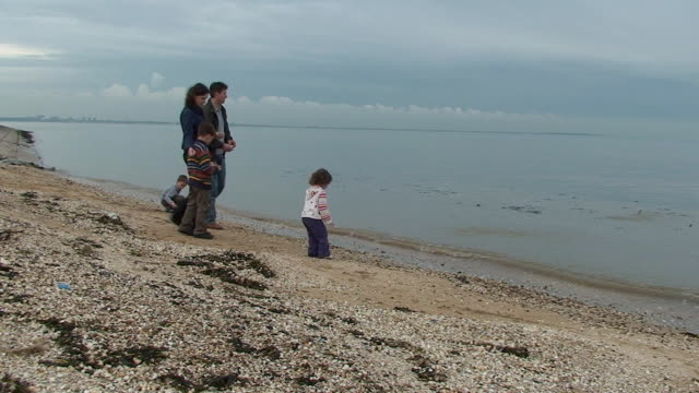 family with three children walking on the coast - family with three children stock videos & royalty-free footage