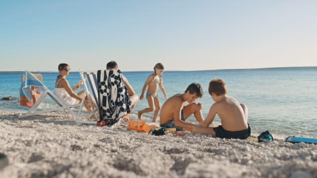 vídeos de stock e filmes b-roll de slo mo family with three kids relaxing on the beach. - baía