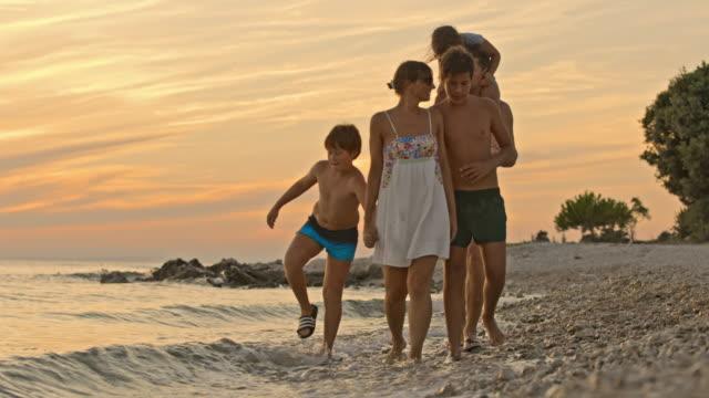 vídeos de stock e filmes b-roll de slo mo family with three kids walking on the beach at sunset - baía