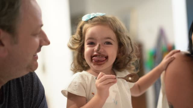 family with twin sibling (down syndrome boy and girl) having fun eating chocolate - pulling funny faces stock videos & royalty-free footage