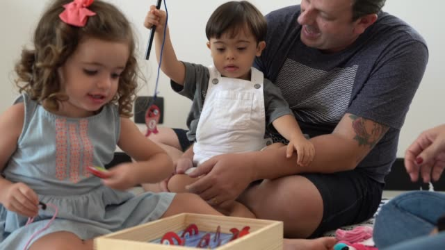 family with twin sibling (down syndrome boy and girl) playing with leisure games - toddler stock videos & royalty-free footage