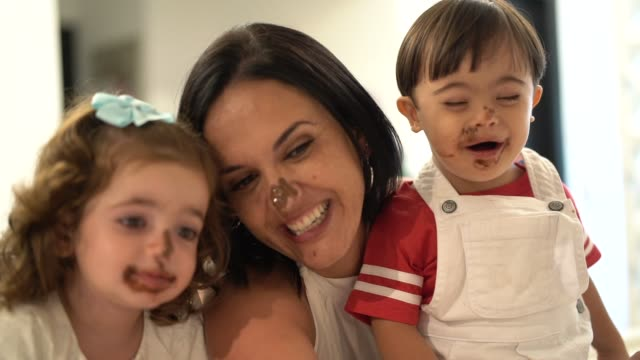 family with twin sibling (down syndrome boy and girl) taking a selfie after eating chocolate - pulling funny faces stock videos & royalty-free footage