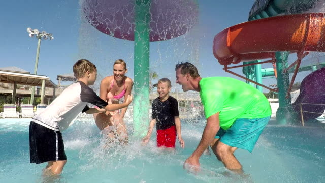 familjen med två pojkar ha kul på vatten park stänk - vattenrutschbana rutschkana bildbanksvideor och videomaterial från bakom kulisserna
