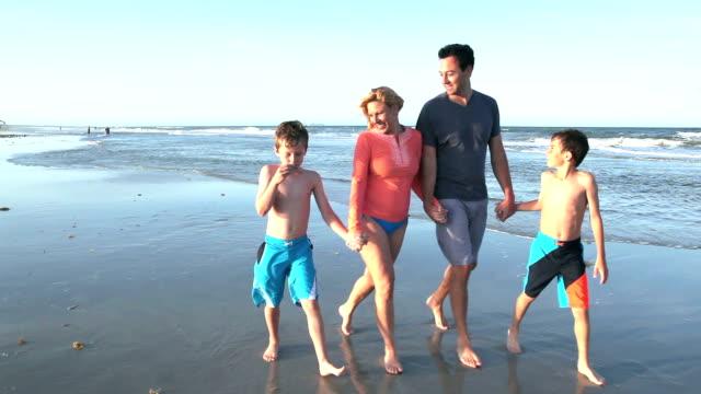 Familie mit zwei jungen Hand in Hand, zu Fuß am Strand