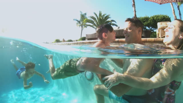 family with two boys playing in swimming pool - underwater camera stock videos & royalty-free footage