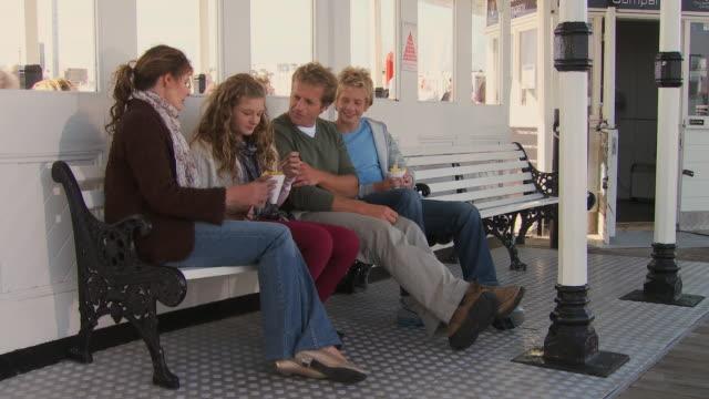 ms, family with two children (10-11, 12-13) eating chips on brighton pier, brighton, sussex, united kingdom - ブライトン パレスピア点の映像素材/bロール