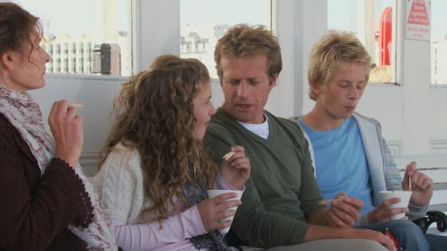 vídeos y material grabado en eventos de stock de cu, family with two children (10-11, 12-13) eating chips on brighton pier, brighton, sussex, united kingdom - patata
