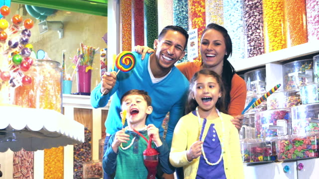 family with two children excited to be in candy store - lollipop stock videos and b-roll footage