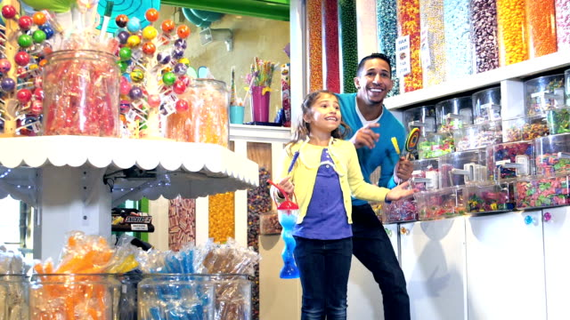 family with two children excited to be in candy store - sweet food stock videos & royalty-free footage
