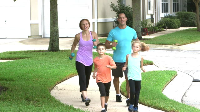 family with two children exercising together - racewalking stock videos and b-roll footage