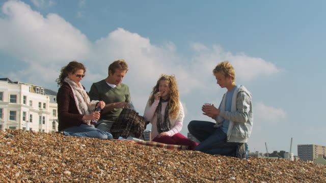 ms, family with two children (10-11, 12-13) having picnic on brighton beach, brighton, sussex, united kingdom - picnic stock-videos und b-roll-filmmaterial