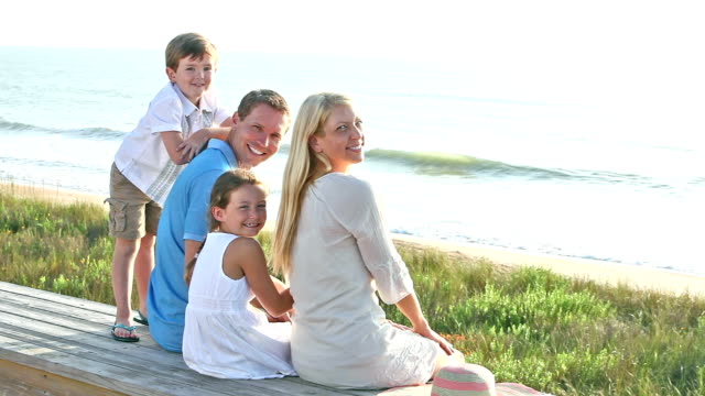 Family with two children laughing together at beach