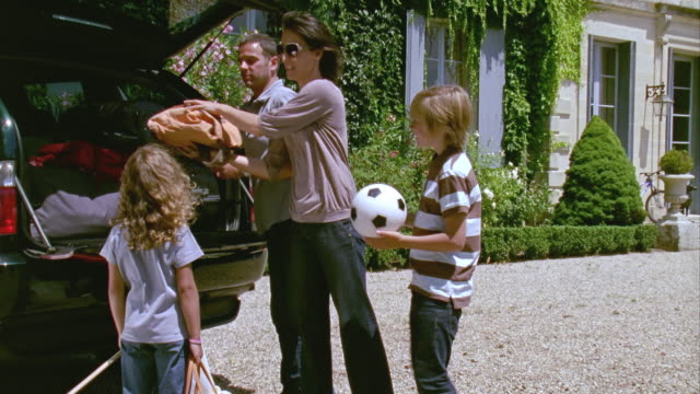 MS, Family with two children (6-7, 12-13) loading luggage into car in front of palace/Saint Ferme, Gironde, France