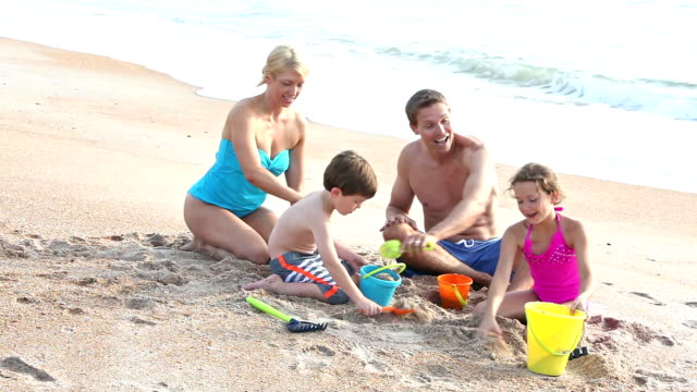 Family with two children playing in sand on beach