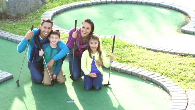 family with two children playing miniature golf - 6 7 years stock videos & royalty-free footage