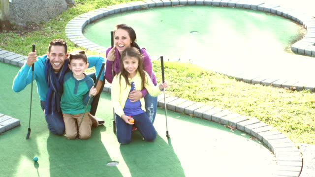 vídeos de stock e filmes b-roll de family with two children playing miniature golf - 6 7 years