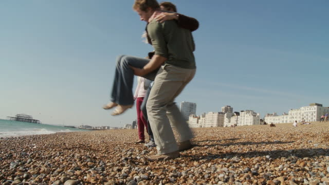 ms, family with two children (10-11, 12-13) playing on brighton beach, rear view, brighton, sussex, united kingdom - carrying stock videos & royalty-free footage