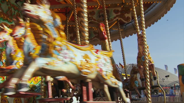 ms, pan, family with two children (10-11, 12-13 )riding carousel on brighton pier, brighton, sussex, united kingdom - ブライトン パレスピア点の映像素材/bロール