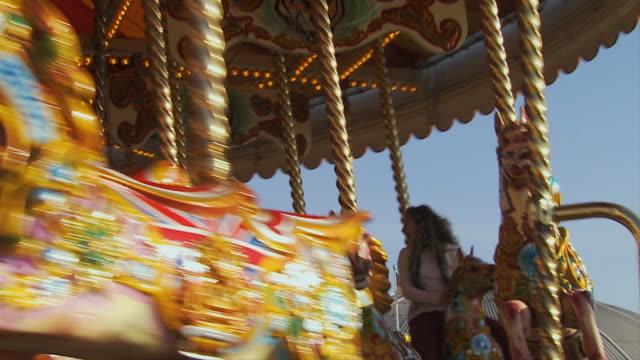 cu, la, family with two children (10-11, 12-13 )riding carousel on brighton pier, brighton, sussex, united kingdom - 12 13 år bildbanksvideor och videomaterial från bakom kulisserna