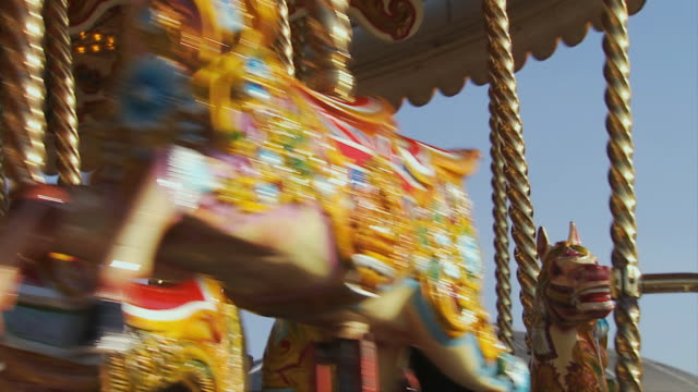 cu, la, family with two children (10-11, 12-13 )riding carousel on brighton pier, brighton, sussex, united kingdom - 回転遊具点の映像素材/bロール