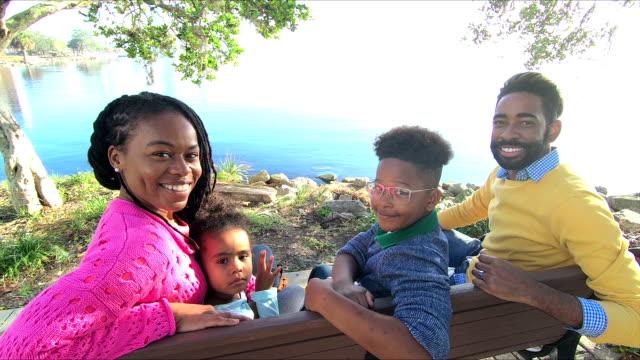 vidéos et rushes de famille avec deux enfants assis sur un banc, l'eau - banc