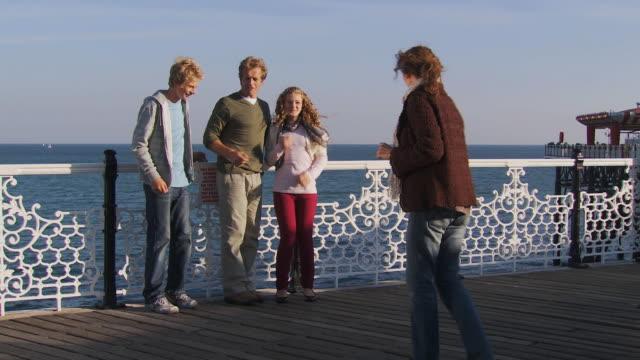 ws, family with two children (10-11, 12-13) taking pictures on brighton pier, brighton, sussex, united kingdom - ブライトン パレスピア点の映像素材/bロール