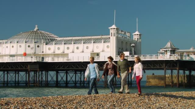 ws, pan, family with two children (10-11, 12-13) walking on brighton beach, brighton, sussex, united kingdom - ブライトン パレスピア点の映像素材/bロール
