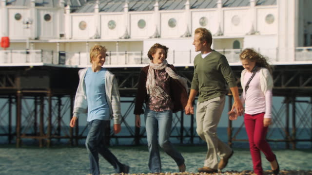 ms, pan, family with two children (10-11, 12-13) walking on brighton beach, brighton, sussex, united kingdom - 10 11 years stock videos and b-roll footage