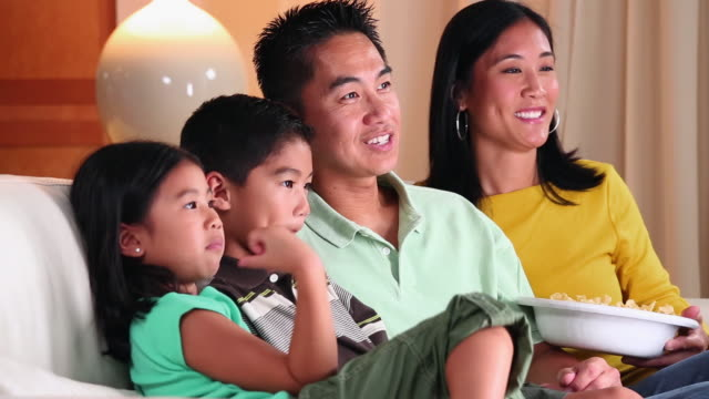 vidéos et rushes de ms pan family with two children watching television on couch / richmond, virginia, usa - regarder attentivement