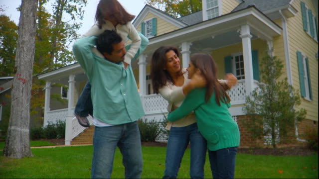 ms, family with two daughters (6-7, 10-11) playing in front of house, portrait, richmond, virginia, usa - dreiviertelansicht stock-videos und b-roll-filmmaterial