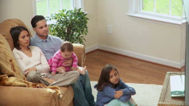 stockvideo's en b-roll-footage met ms, pan, family with two daughters (6-1 months, 8-9) watching television in living room, richmond, virginia, usa - 6 11 maanden