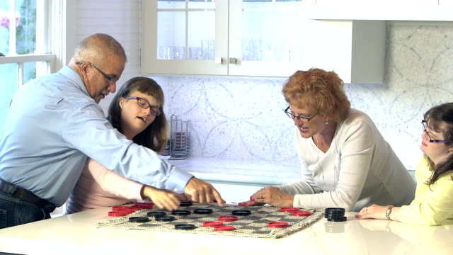 Family with two down syndrome girls playing checkers