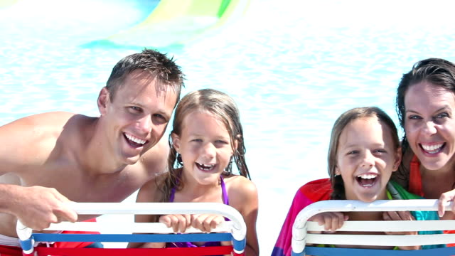 vídeos de stock e filmes b-roll de family with two girls having fun at swimming pool - equipamento de parque infantil