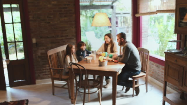 family with two kids having breakfast at home - dining table stock videos & royalty-free footage
