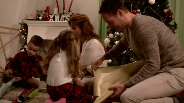family with two little kids enjoying wrapping christmas presents together - christmas wrapping paper stock videos & royalty-free footage