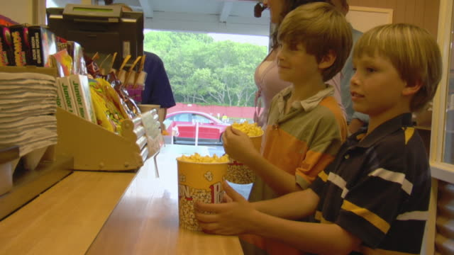 vídeos y material grabado en eventos de stock de ms, family with two sons (8-9, 10-11) buying pop corn and leaving snack bar, wellfleet, cape cod, massachusetts, usa - palomitas