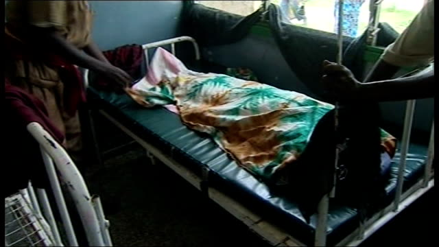 Cholera threat to famine victims Body of woman lying on hospital bed is covered with sheet by her husband
