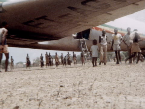 bume views of parched land landing strip seen from cockpit as plane lands children and villagers running to plane as held back by armed soldiers food... - スーダン点の映像素材/bロール