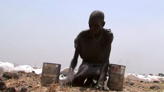 famine declared as 100,000 people face starvation; south sudan: ganyiel: ext various shots of men and women carrying large sacks of un food aid... - other stock videos & royalty-free footage