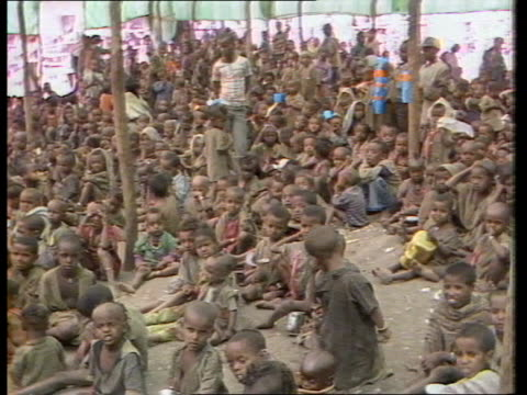 geldof accuses government of failing to feed people as he returns to country; cutaways tx:15.2.84 ethiopia: ext tms children seated on ground in camp... - ethiopia stock videos & royalty-free footage