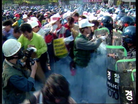 stockvideo's en b-roll-footage met famine north korea famine itn seoul seq protesters clashing with riot police at may day rally int professor euigak hwang into office and puts book on... - korea