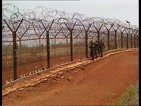 famine north korea famine itn south korean soldiers patrolling border fence tgv along top of border fence - north korea stock videos & royalty-free footage
