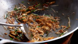 Famous Asian Thai street fast food in a hot pan, Pad Thai, is a stir-fried rice noodle dish commonly served as a street food and at casual local eateries in Thailand.