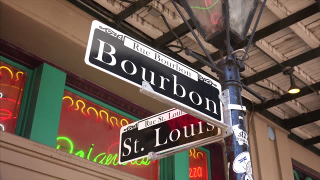 famous bourbon street road sign in the french quarter of new orleans, louisiana comes into focus - bourbon street new orleans stock videos and b-roll footage