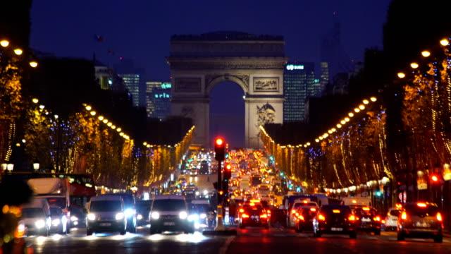stockvideo's en b-roll-footage met beroemde champs-elysées en de arc de triomphe in schemerlicht in parijs - brede straat