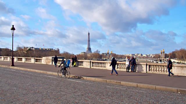 パリの橋から遠く離れた場所に見える有名なエッフェル塔。サイクラーおよび歩行者 - エッフェル塔点の映像素材/bロール