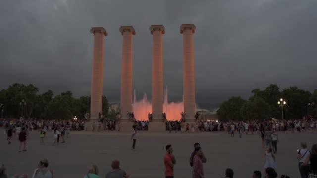 vídeos y material grabado en eventos de stock de famous landmark surrounded by tourists in city against sky at dusk - barcelona, spain - fuente estructura creada por el hombre
